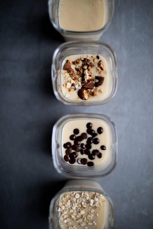 Plusieurs pots de crème vanille avec différents accompagnements (chocolat, musli, etc)