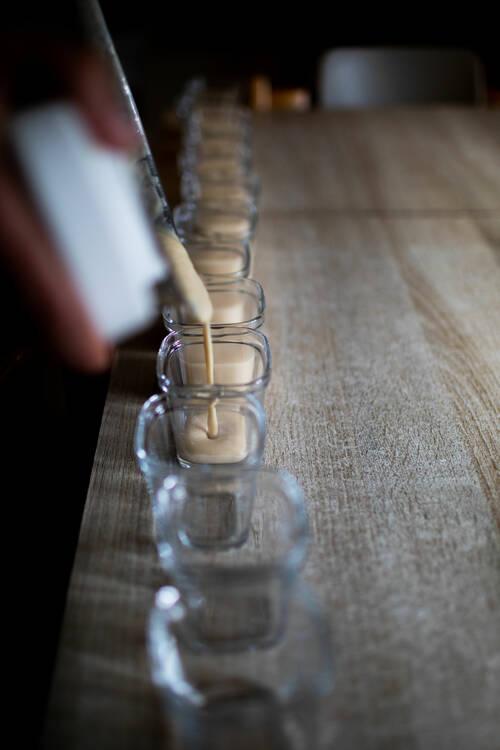 Une dizaine de pots alignés dans lesquels on est en train de verser la crème.