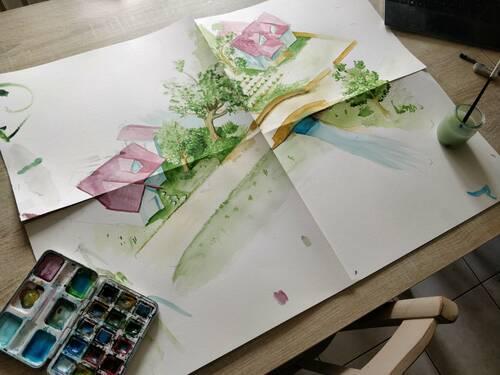 Aquarelle d'un petit village en vue isométrique. Posée sur une table avec des pinceaux et de la peinture autour.